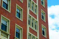 En röd byggnad mot den blåa himlen arkivfoton