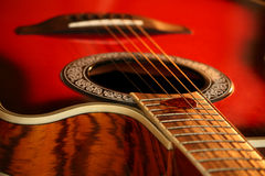 En röd gitarr och en hacka Arkivfoto