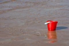 En röd hink absorberar tidvattnet som kommer in i stranden royaltyfri fotografi