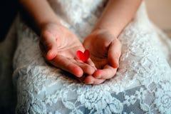 En röd hjärta i händer Fotografering för Bildbyråer