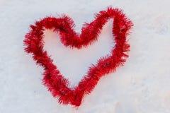 En röd hjärta i snön som göras av jul, binder Arkivfoto