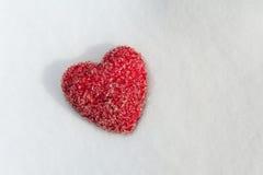 En röd hjärta som ligger på Snow Fotografering för Bildbyråer