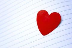 En röd hjärta på Notebook' s-sida royaltyfri foto