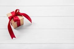 En röd julgåva på vit träbakgrund med ett stort arkivfoton