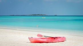 En röd kajak på den vita sandstranden och turkoslagun i Maldiverna arkivbild