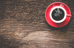 En röd kopp kaffemorgon på den gamla trätabellen Fotografering för Bildbyråer
