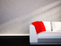 En röd kudde är på soffan Royaltyfri Bild