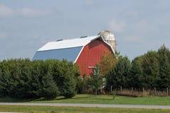 En röd ladugård och silo mot blå himmel Royaltyfri Foto
