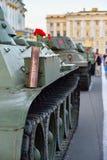 En röd nejlika i facket på en tung sovjetisk behållare KV-1 på Arkivbild
