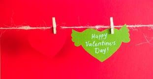 En röd pappers- hjärta och en grön hjärta med lyckönskan och vingar fixade med klädnypor på en kabel Röd bakgrund Royaltyfria Bilder