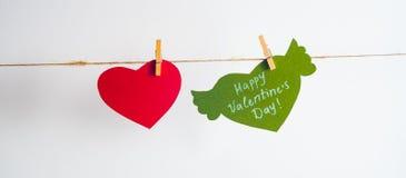 En röd pappers- hjärta och en grön hjärta med lyckönskan och vingar fixade med klädnypor på en kabel Vit bakgrund Royaltyfri Foto