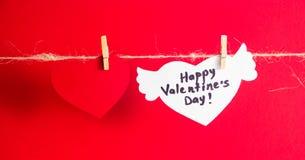 En röd pappers- hjärta och en vit hjärta med lyckönskan och vingar fixade med klädnypor på en kabel Röd bakgrund Royaltyfri Bild