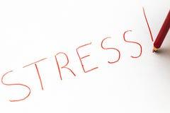 En röd pastellfärgad blyertspenna som ut skriver det stressat för ord Arkivbilder