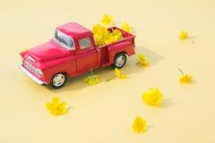 En röd retro bil med guling blommar på en rosa bakgrund Arkivbilder