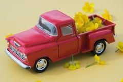 En röd retro bil med guling blommar på en rosa bakgrund Royaltyfria Foton