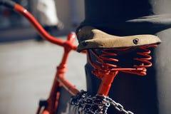 En röd retro cykel med ett gammalt piskar sadeln royaltyfri bild