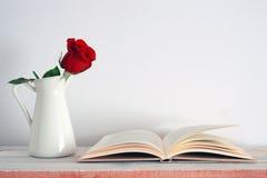 En röd rosblomma i en vit tappningvas bredvid en öppen bok royaltyfri fotografi