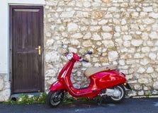 En röd sparkcykel framme av ett gammalt stenhus Royaltyfri Bild