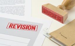 En röd stämpel på ett dokument - revidering arkivbild