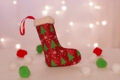 En röd strumpa med julgranar för handgjorda gåvaställningar mot bakgrunden av julljus och mjuka bollar royaltyfria foton