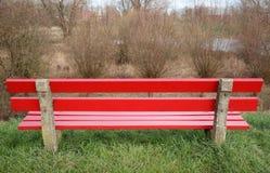 En röd träbänk Arkivbild