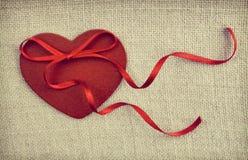 En röd trähjärta med en ribonpilbåge på tappningtygbackgroun Arkivbild