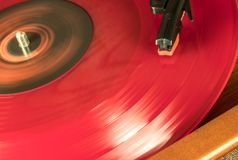 En röd Vynil diskett spinneds i en spelare royaltyfri foto