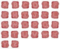 En rödaktig Brown sten av alfabetbokstäver Arkivfoton