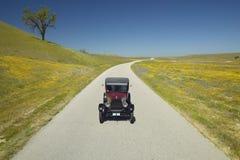 En rödbrun modell T som kör ner en scenisk väg som omges av vårblommor av av rutt 58, Shell Road, CA Royaltyfri Bild