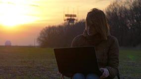 En rödhårig flicka använder bärbara datorn nära radar i fält under solnedgång arkivfilmer