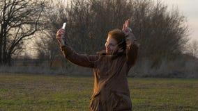 En rödhårig flicka gör en selfie med en smartphonekamera nära träd stock video
