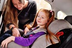 En rödhårig flicka ler i bilen arkivbild