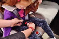 En rödhårig flicka ler i bilen royaltyfria foton