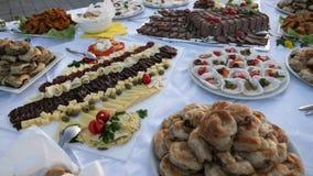 En rörande längd i fot räknat av en svensk tabell som väntar på gästerna att ta någon mat på deras plattor stock video