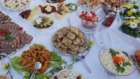 En rörande längd i fot räknat av en svensk tabell som väntar på gästerna att ta någon mat på deras plattor lager videofilmer