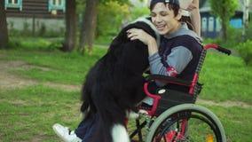 En rörelsehindrad person spelar med en hund, canitisterapi, handikappbehandling till och med utbildning med en hund, man i a