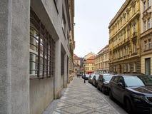 En rad av bilar som parkeras på sidan av vägen av en trottoar i en stad med byggnader arkivbild