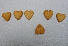 En rad av bruna hjärtor från kakor på en grå bakgrund Arkivfoto