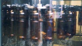 En rad av bruna plast- flaskor är rotera och få pastöriserad arkivfilmer