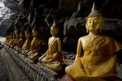 En rad av Buddhastatyer i grottan Royaltyfria Bilder