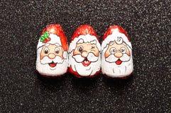 En rad av choklad som täckas med Santa Clauses, vänder mot omslag Arkivfoto