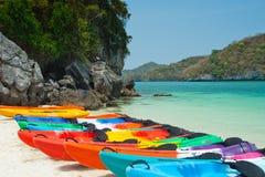 En rad av den färgrika kajaken väntar på den klara nollan för stranden havet Royaltyfri Fotografi