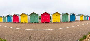 En rad av den färgrika trästranden förlägga i barack på stranden i Eastbourne Arkivbild