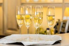 En rad av exponeringsglas som fylls med champagne, är uppställt klart att tjänas som Royaltyfri Bild