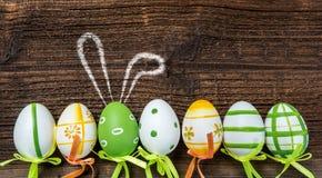 En rad av fem färgrika easter ägg med kaninen gå i ax på träBac Arkivfoton