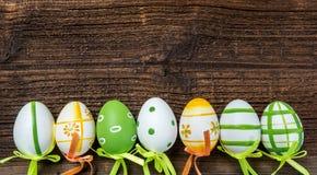 En rad av fem färgrika easter ägg på träbakgrund Royaltyfri Foto