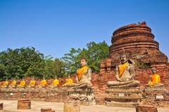 En rad av forntida buddha statyer av fördärvar framme pagoden Arkivfoton