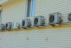 En rad av gråa luftkonditioneringsapparater på en brun vägg av en byggnad med ett fönster royaltyfri foto