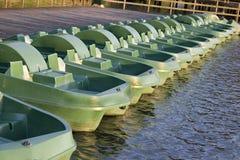 En rad av gröna fartyg på träpir på sjön i sommar Arkivfoto