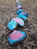 En rad av kulöra stenar på jordningen fotografering för bildbyråer